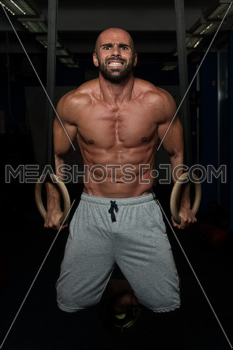 Adult Man Exercising While Holding Large Gymnastic Rings At The Gym