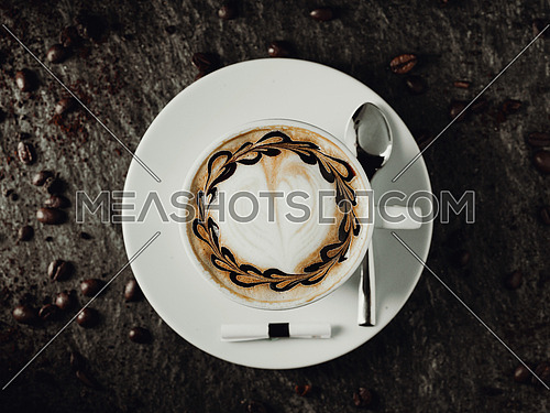 cup of coffee on a black wooden table surrounded by coffee beans. View for top
