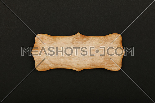 Figured ornately shaped blank wooden sign with copy space in center of black paper background, title slide template