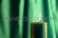 Teal candle trembling flame close up out of the dark green folded fabric cloth background, off-center