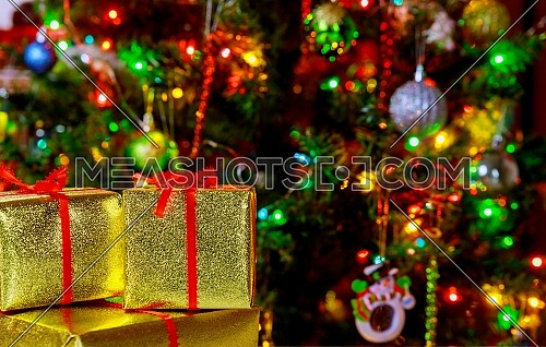Christmas holiday background. Gifts with a red ribbon, a christmas tree and decor gift boxes