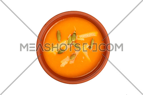 Ceramic bowl of pumpkin cream soup with seeds and cheese isolated on white background, top view