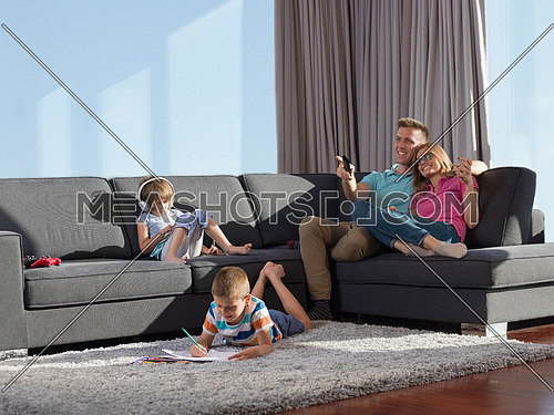 Happy Young Family Playing Together at home using a tablet and a children's drawing set