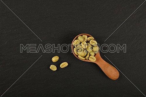 Close up one wooden scoop spoon full of unroasted raw green Arabica coffee beans over black slate background, elevated top view, directly above