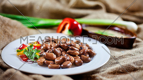 this is a shot for Egyptian beans (foul) on a brown cloth with onions and pepper... egyptian breakfast