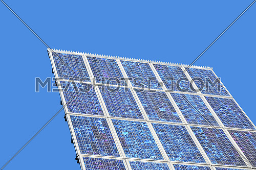 Close up photovoltaic solar panel over clear blue sky with copy space, low angle view