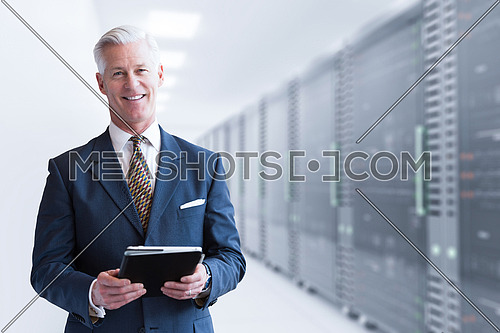 Portrait of senior businessman in big rack server room