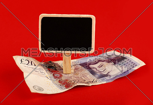 Close up one twenty British pounds paper currency banknote and blank chalk blackboard sign with copy space over red background, high angle view