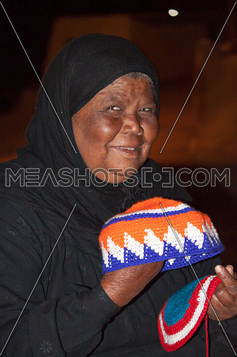 Old Woman holding hand made nubiean hats