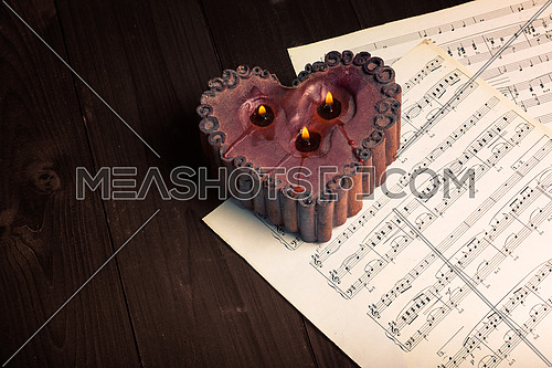 In the picture lit candle with the shape of heart, aged pages of sheet music and wooden background,used split tonig for old/vintage style.