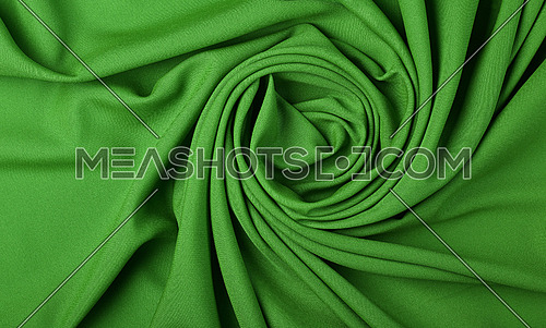 Close up abstract textile background of spiral shaped green folded pleats of fabric, elevated top view, directly above