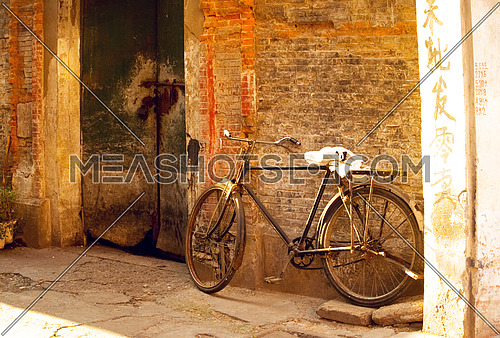 shanghai old bicycle over a brick walland old door