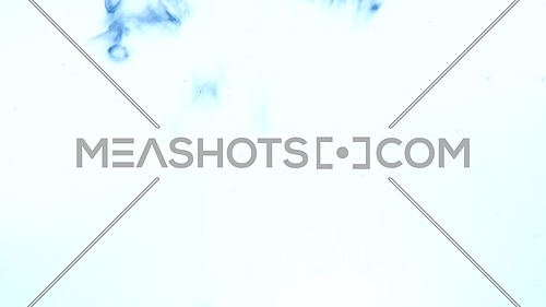 Extreme close up abstract background of air bubbles emerging underwater over white background in blue light, low angle side view, slow motion
