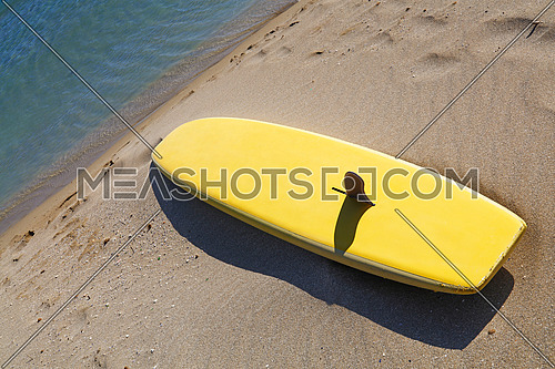 Close up one yellow surfing board on sand sea beach, high angle view, personal perspective