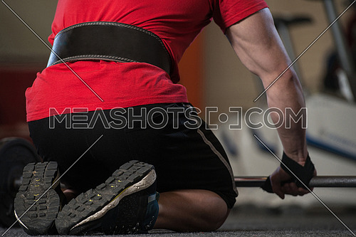 Bodybuilder Prepairing For Deadlift Putting Straps For Safety