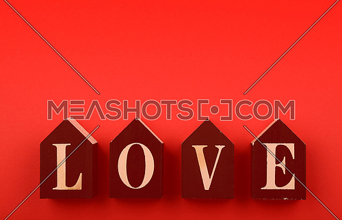 Wooden house shaped cube signs with LOVE word over red background and copy space, low angle view