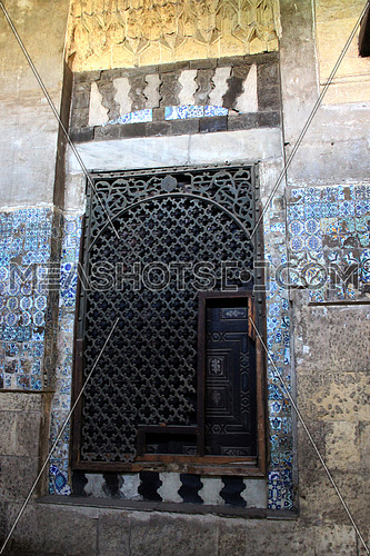 a photo from inside a historical mosque in Islamic Cairo, Egypt showing old doors and architecture and artistic style used at that time