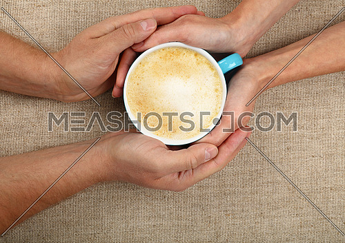 Man and woman hands holding and hugging together big full cup of latte cappuccino coffee with frothy milk over canvas tablecloth, close up, elevated top view