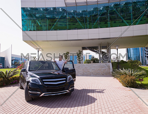 successful young businessman with luxury car in front of corporate business building