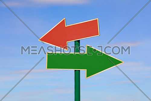 Road signpost with two blank copy space arrows, green and red, directing to different directions, left and right, over clear blue sky, low angle side view