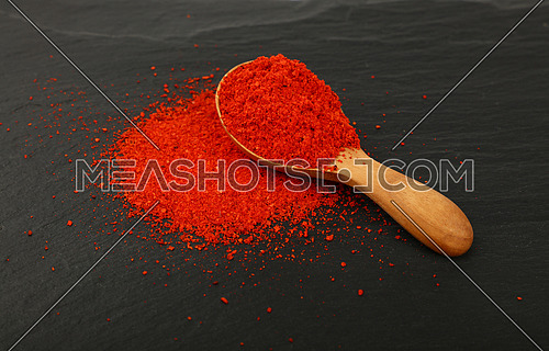 Close up one wooden scoop spoon full of red chili pepper or paprika powder on background of black slate board, high angle view