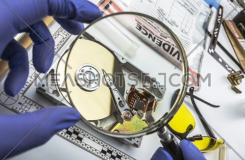 Police expert examines with magnifying glass hard drive in search of evidence, conceptual image