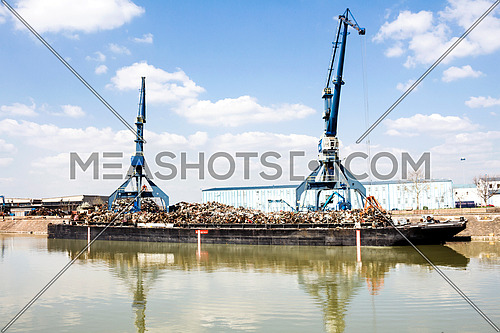 Crane operating in the recycling area while reflecting out of water