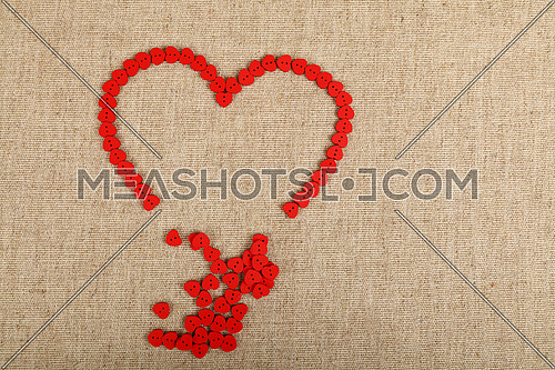 Red heart shaped handmade wooden sewing buttons broken frame on linen canvas, elevated top view, close up