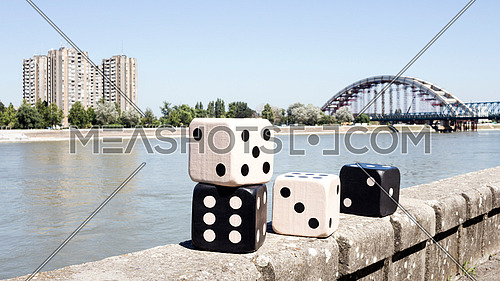 Dices Resting On The Wall With River And Cityscape in Background