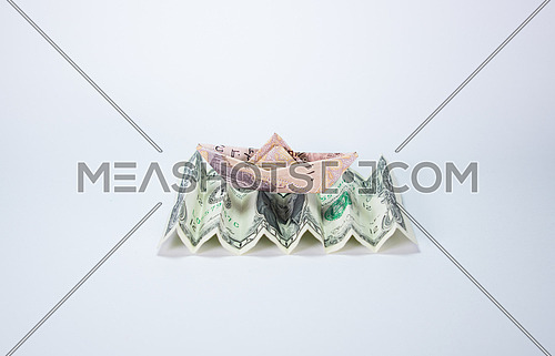 one Egyptian Pound folded like paper boat floating on one dollar bill concept