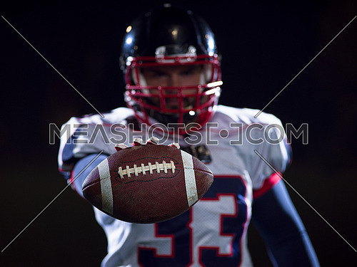 portrait of confident American football player holding ball while standing on field at night