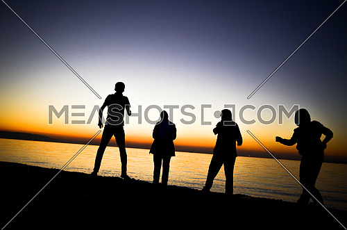 4 friends standing at the beach during sunset magic hour