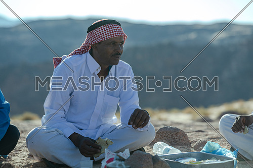 Portirat for a bediuon male wearing traditional clothing and eating in Sinai at day.