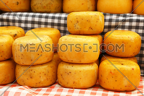 Close up selection of whole small heads of hard cheese on retail display, low angle view