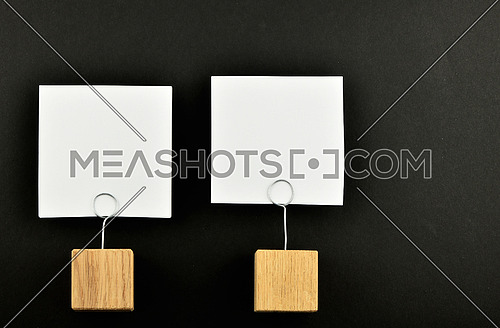 Two white paper notes with wooden holders isolated at black paper background for presentation