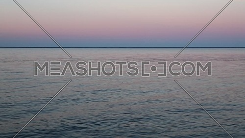 Waterscape of waves and ripples run in the wind on blue water surface of lake under clear purple and pink evening sunset sky, high angle view