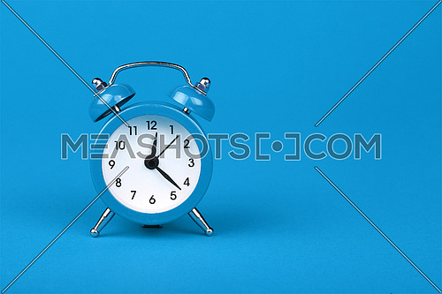 Close up one small blue metal twin bell retro alarm clock over light blue paper background with copy space, low angle front view