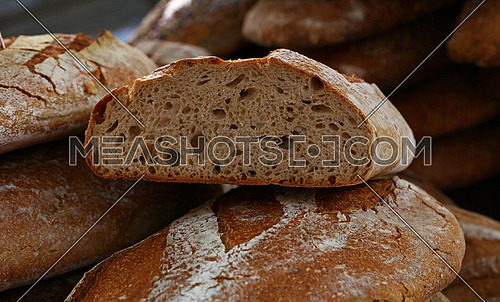 Close up selection of fresh bread loaves on retail display of bakery store, low angle view