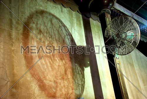 a vintage looking fan with shadow on the wall