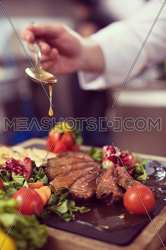 Chef hand finishing steak meat plate with Finally dish dressing and almost ready to serve at the table