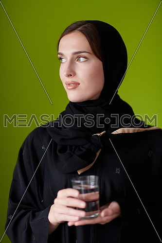 Modern Muslim Woman in Abaya Holding a Date Fruit and glass of water in from of her. Concept celebration of iftar in ramadan and end of feasting