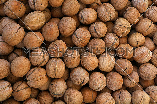 Whole walnuts with brown nutshells on retail market, close up, background, high angle view