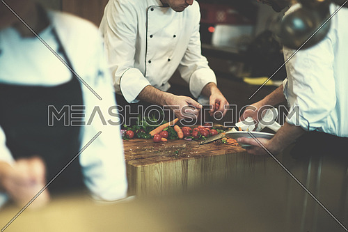 Professional team cooks and chefs preparing meal at busy hotel or restaurant  kitchen