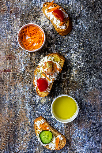 Top shot of pieces of toast with cheese, cucumber, tomatoes,carrots and olive oil on marble table.
