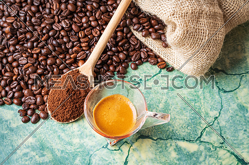 Coffee beans in coffee burlap bag on green table,wooden spoon with ground coffee on top and coffee glass cup, view from above