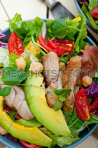 fresh and healthy Chicken Avocado salad over rustic wood table