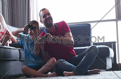 father and son play video game in beautifull apartment