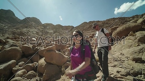 Reveal shot for a tourists couple climbing down big rocks explore Sinai Mountain for wadi Freij at day.