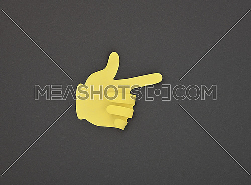 Paper made yellow hand gesture sticker pointing with index finger over grey background