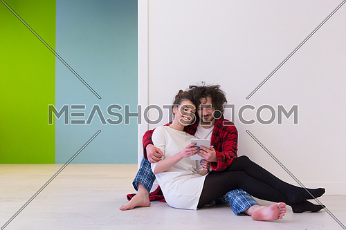 Young Couple sitting on the floor and using interent on digital tablet